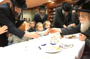Toldos Aharon Rebbe handing mezonos to children of the Los Angeles Cheder