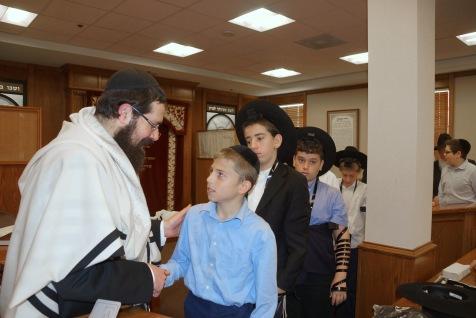 The Rosh Hayeshiva greeted by students of Yeshiva Rav Isacsohn following Shacharis. Photos: Arye D. Gordon
