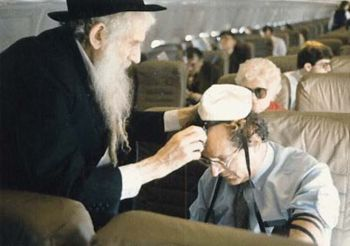 Rabbi Raichik helping a fellow Yid with the Mitzva of Tefillin