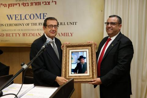 Chairman of the Board CPA Moshe Leon presenting Rabbi Ryzman with the photo of the kevias mezuzah at the Institute by Harav Steinman