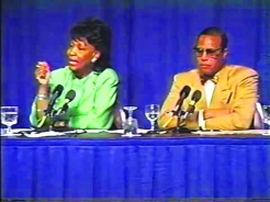 A screenshot of a town hall meeting in 1993 on 'Race in America.' Rep. Maxine Waters is sitting next to Farrakhan